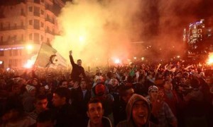 Fans of Algeria's soccer team hold the country's national flag as they celebrate in downtown Algiers