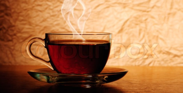 Glass cup of black tea on wooden table with smoke